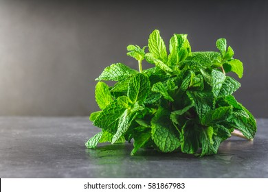 A bunch of mint tied with twine on a gray background.
