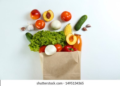 Bunch of mixed organic fruits, vegetables & greens, gourmet pile in full eco friendly shopping bag to reduce ecological footprint. Zero waste concept. White table background, copy space, close up.