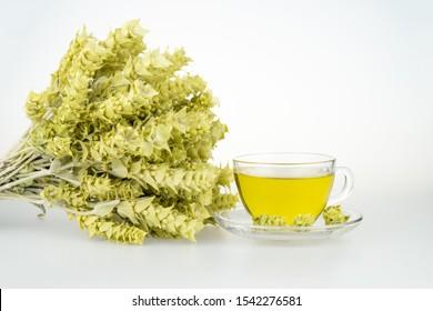 Bunch of mountain tea Malotira and mug with hot tea. Greek traditional herbal tea in transparent cup. Mountain tea sideritis. Natural Greek herbs.