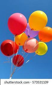 bunch of multicolored balloons in the city festival on blue sky background, vertical composition