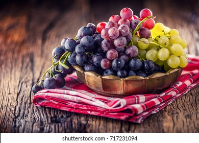 Bunch of multicolored grapes in retro bowl on old oak table.