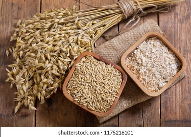 bunch of oat ears, cereals and grains on wooden table, top view