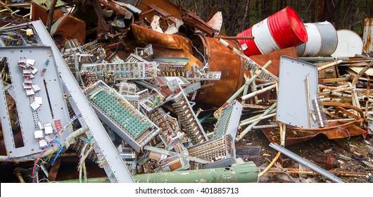Bunch of old broken equipment on street (electronic junkyard, electronic components, electronic instrumentation, computer stuff, mains), empty barrels of fuel