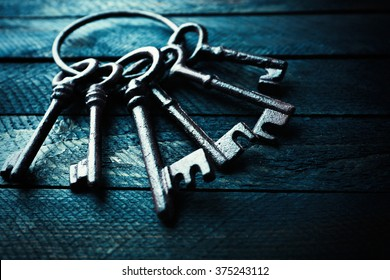 Bunch of old keys on dark wooden background, close up