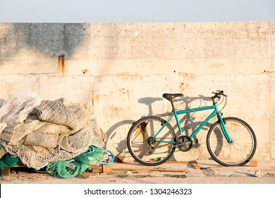 Bunch of old weathered trawl fishing nets and a parked bicycle on fishing village pier on a sunny day