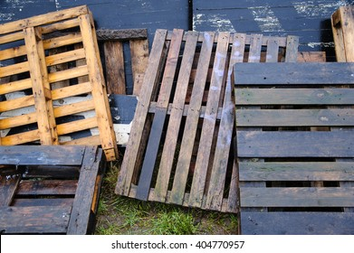 Bunch of old wet colored wooden pallets on green grass