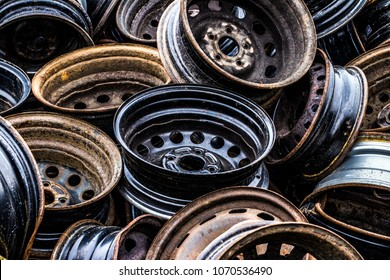 A bunch of old wheel rims on the car dump.
