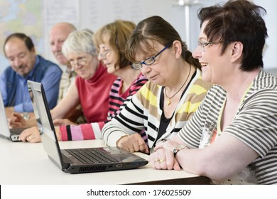 A bunch of older people looking at computers in a classroom.