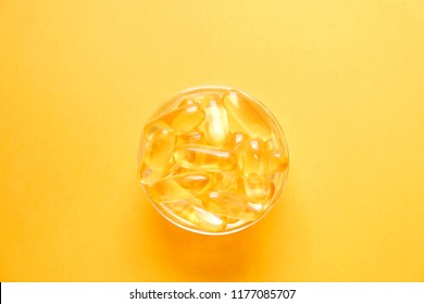 Bunch of omega 3 fish liver oil capsules in small glass bowl. Close up of golden translucent pills in pile. Healthy every day fatty acids nutritional supplement dosage. Top view, flat lay, copy space.