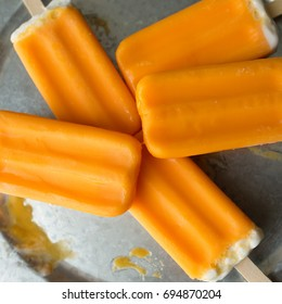 A bunch of orange creamsicle treats on a galvanized tray.