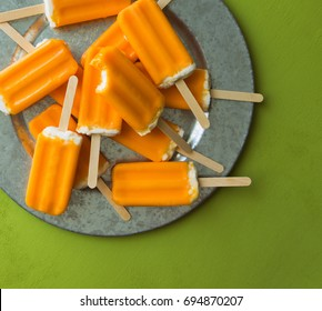 A bunch of orange creamsicle treats on a galvanized tray. Overhead shot.