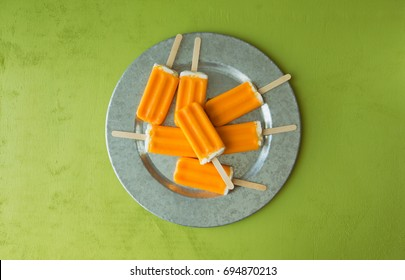 A bunch of orange creamsicle treats on a galvanized tray. Top view.