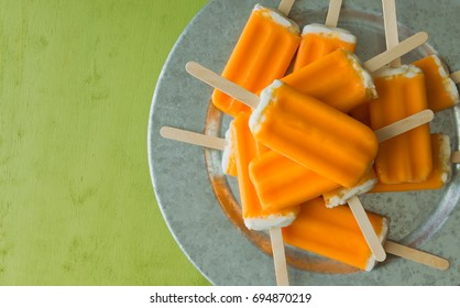 A bunch of orange creamsicle treats on a galvanized steel tray. Over head shot.
