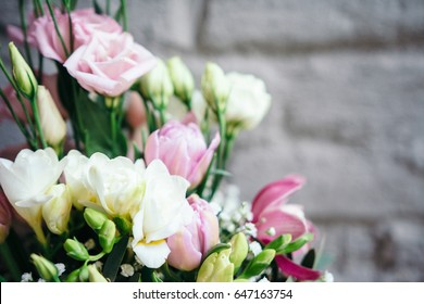 Bunch of orchids, tulips, peonies, freesias and pink eustoma flowers. Bouquet of fresh flowers in pink colors on a gray wall. Close up