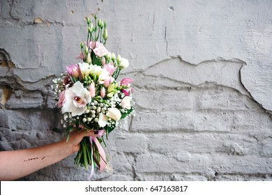 Bunch of orchids, tulips, peonies, freesias and pink eustoma flowers in woman's hand. Bouquet of fresh flowers in pink colors on a gray wall with copy space