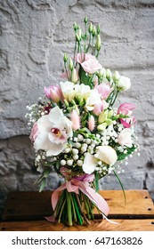 Bunch of orchids, tulips, peonies, freesias and pink eustoma flowers. Bouquet of fresh flowers in pink colors on a gray wall