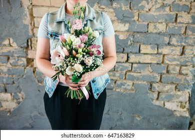 Bunch of orchids, tulips, peonies, freesias and pink eustoma flowers in woman's hand.. Bouquet of fresh flowers in pink colors on a brick wall.