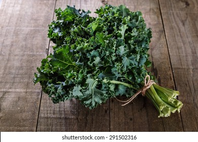 Bunch of organic kale on a rustic wooden background. Selective focus