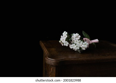 A bunch of pale pink flowers on a wooden table in front of black background. The pink paper tied on its stem is a love letter,  intimating the fumitsuke-eda in in Heian period in Japan.