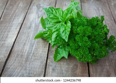 bunch of parsley and basil on wooden surface