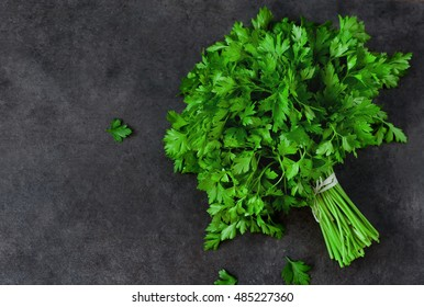 Bunch of parsley isolated on a black background with space for text. Top view.