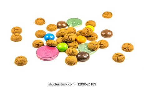 Bunch of pepernoten cookies, sweets and chocolate money frontal view on white background for annual Sinterklaas holiday event in the Netherlands on december 5th