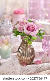 bunch of pink flowers in vase on the table in romantic shabby chic style interior