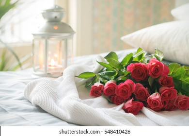A bunch of pink roses on white crochet cardigan, white pillows, small silver lamp and tree at background, a surprise Valentine's Day in bed, soft color tone