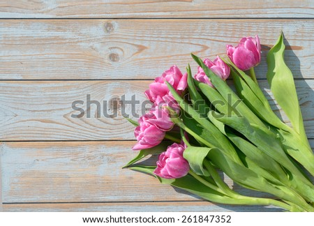 cf2f7e0787b33 bunch of Pink tulips on a old wooden background with sunlight and shadow.  The wood