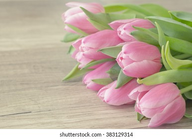 Bunch of pink tulips on wooden surface