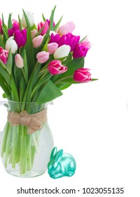Bunch of pink and violet tulips flowers in vase with easter bunny isolated on white background