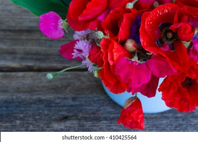 Bunch of Poppy, sweet pea and corn flowers  close up  on wooden background