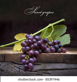 A bunch of purple grapes with leaves lying on a wooden background