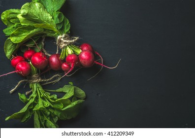 Bunch of radish with leaves on black background, top view, copy space