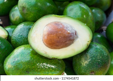 Bunch of raw ripe organic avocados whole and halved at farmers market. Kernel pit silky flesh texture. Seasonal harvest crop local produce concept. Authentic lifestyle image