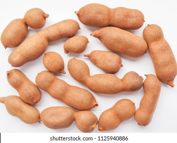 a bunch of raw tamarind fruits over white background