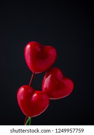Bunch of red glossy hearts on black background. Symbol of love and Valentine's day