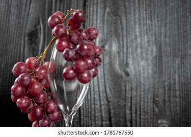 Bunch of red grapes and champagne glass with dark wood background