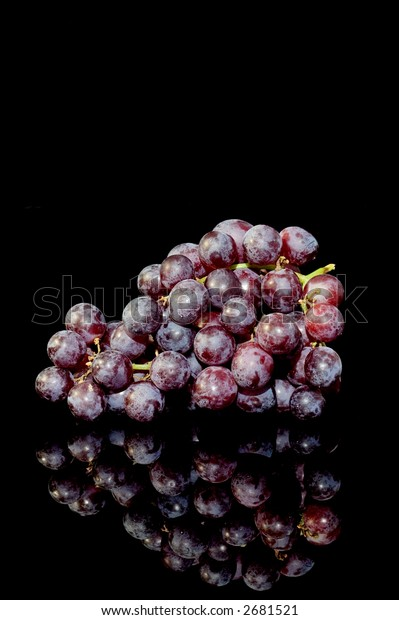 Bunch of red grapes on a black background with reflection