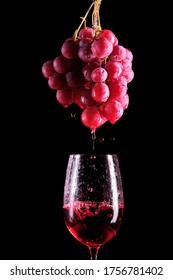 A bunch of red grapes with which red wine drips into a glass.