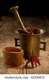 Bunch of red hot cayenne pods, bronze pounder and milled chilli pepper in wooden bowl on wooden table and black background
