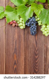Bunch of red, purple and white grapes on wooden table background with copy space