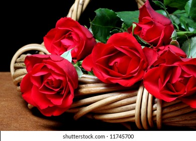 bunch of red roses laying in caneware basket