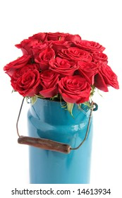 Bunch of red roses in an old-fashioned milk churn isolated on white