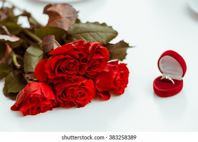 Bunch of red roses, wedding ring and love  - all you need for marriage proposal! On a white background