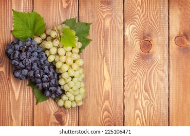 Bunch of red and white grapes on wooden table background with copy space