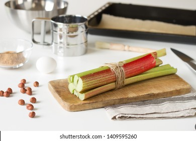 Bunch of rhubarb is on a wooden deck with kitchen supplies as a process of cake baking