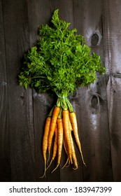 Bunch of ripe carrots on a black wooden background