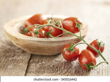 Bunch of ripe fresh mini san Marzano vine tomatoes displayed half in half out of a small wooden dish over a wood background