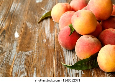 Bunch of ripe organic peaches in pile on brown grunged wood textured table. Local produce harvest heap on vintage wooden countertop. Clean eating concept. Background, top view, close up, copy space